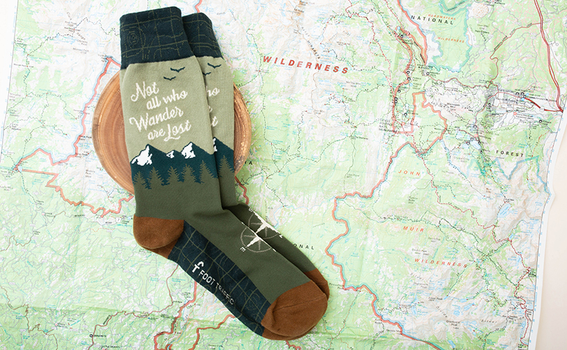 "Men's socks that say ""Not all who wander are lost"" lying on a map"